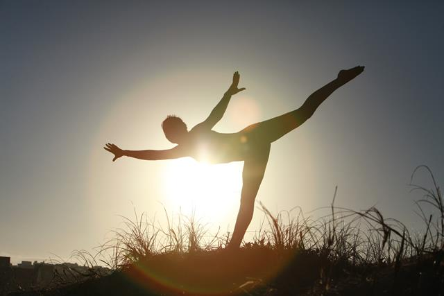 Woman practicing yoga in the sun